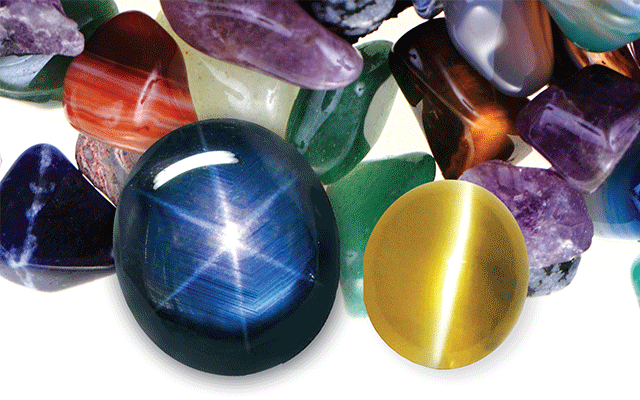 L to R: Blue sapphire with asterism; yellow topaz with chatoyancy against background of assorted gemstones.
