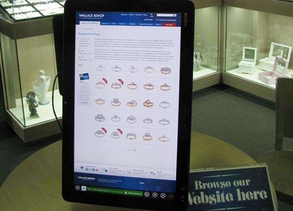 An interactive tablet sits on the counter where customers are encouraged to browse through the website.