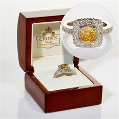 The platinum ring has a cushion-cut yellow diamond surrounded by white diamonds