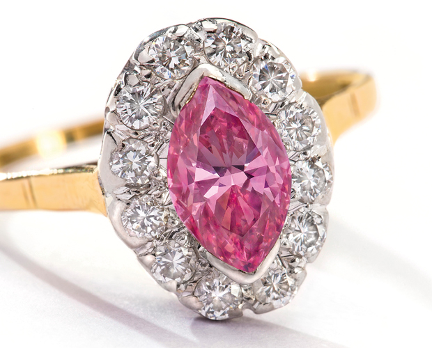 The marquise-shaped pink diamond is set in an 18-carat gold ring, surrounded by brilliant cut diamonds