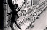 Harold Lloyd dangling from a large clock in his iconic scene from Safety Last!, a 1923 silent romantic comedy.
